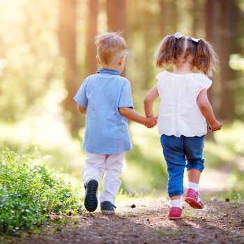 Boy and girl walking in the forest in summer. Children in the forest